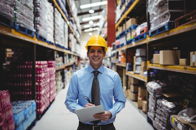 Smiling warehouse manager writing on clipboard in warehouse Premium Photo