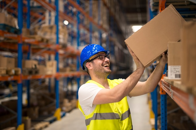 Улыбающийся работник склада, перемещающий коробки на полке Бесплатные Фотографии