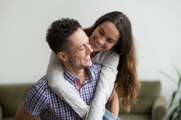 Smiling wife laughing embracing young husband piggybacking her at home Free Photo