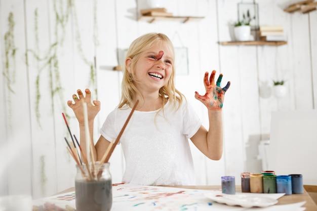 Sorridendo con i denti piccola bionda sveglia che mostra le sue mani in pittura. allegra bambina di sette anni occupata con disegni senza disordine. Foto Gratuite