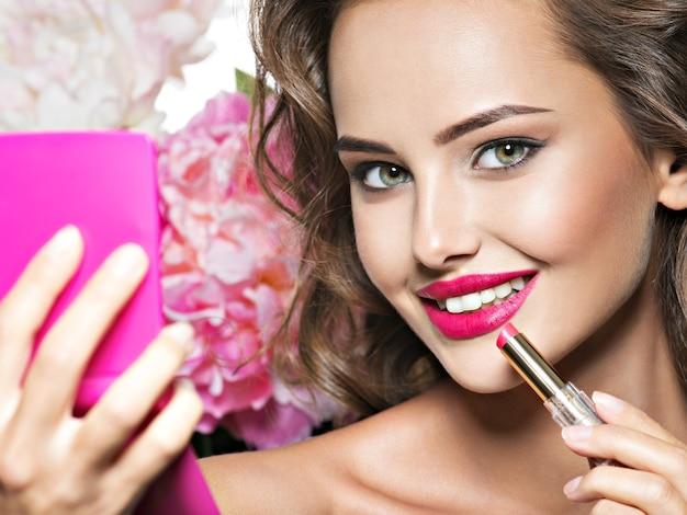 립스틱을 적용하는 웃는 여자. 아름다운 소녀 메이크업 무료 사진