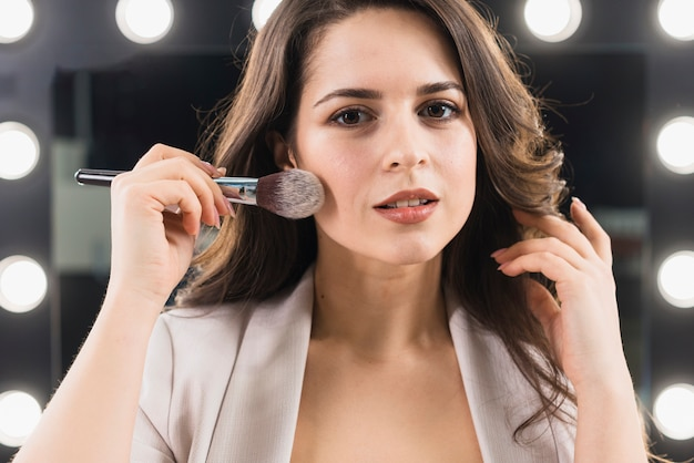 Smiling woman applying makeup on mirror background Free Photo