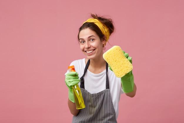 Donna sorridente in grembiule e guanti di gomma che mostrano spugna ordinata e detersivo isolato Foto Gratuite