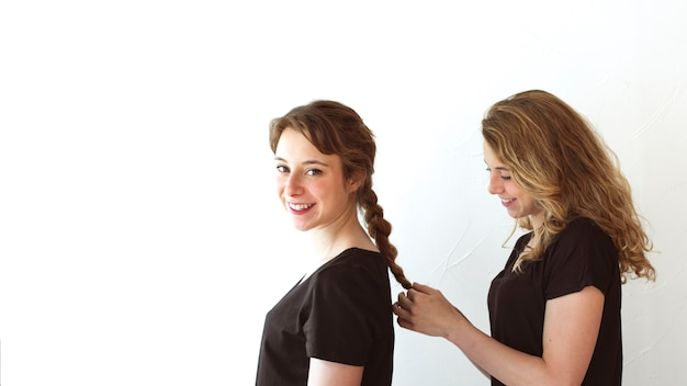Smiling woman braiding her sister's hair isolated over white backdrop Free Photo