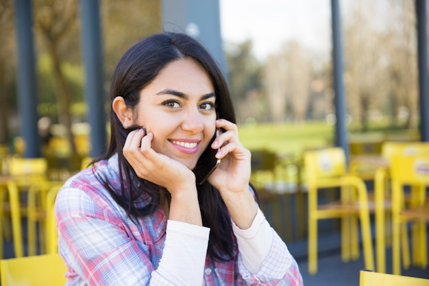 Smiling woman calling on mobile phone in outdoor cafe Free Photo
