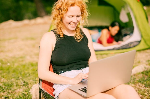 Smiling woman chatting on laptop outdoors Free Photo