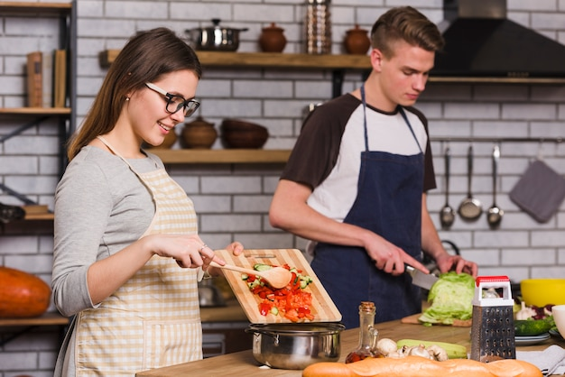 Smiling woman cooking salad with boyfriend Free Photo