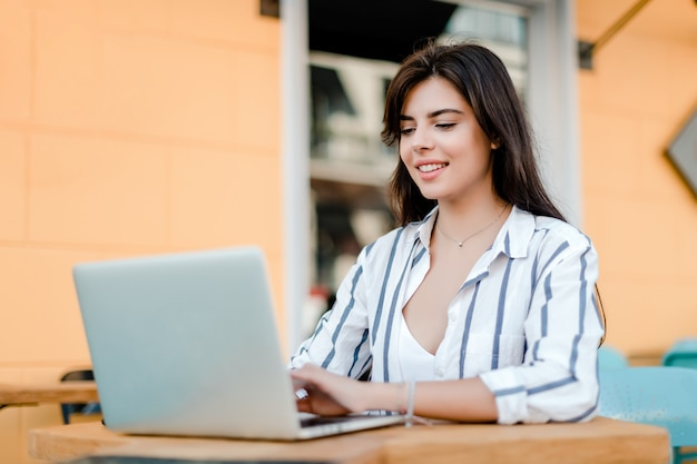 Smiling woman doing freelance work on laptop in cafe outdoors Premium Photo