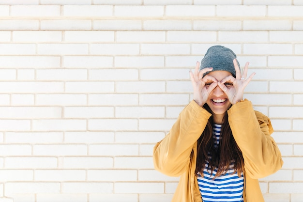 Улыбающаяся женщина делает нормально жест, как бинокль в пиджаке и вязаной шапке Бесплатные Фотографии