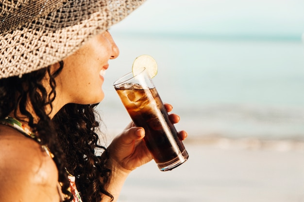 Smiling woman drinking cooling beverage Free Photo