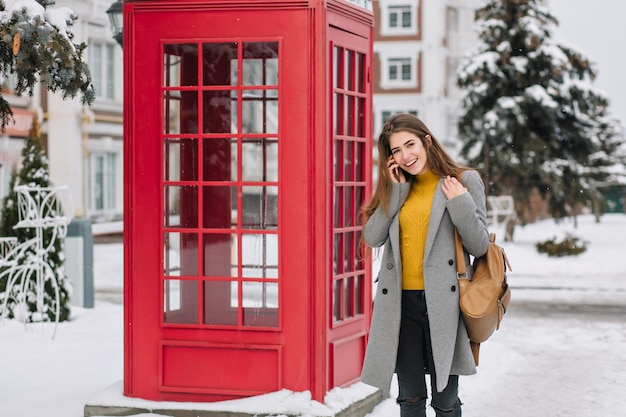Smiling woman in elegant attire talking on smartphone while standing near british phone booth in winter. outdoor photo of pleased brunette woman in trendy coat carrying brown backpack during walk. Free Photo