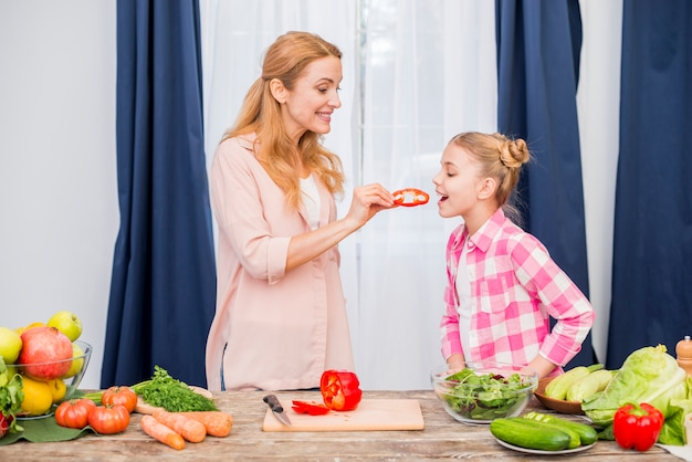 Smiling woman feeding the slice of bell pepper to her daughter Free Photo