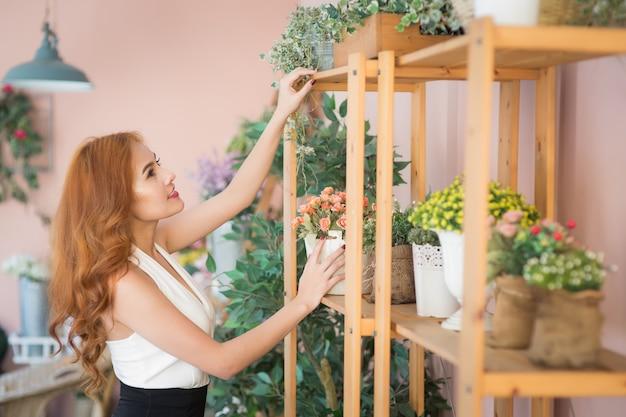 Smiling woman florist arrange beautiful flowers at flower shop Premium Photo