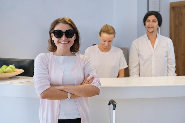 리셉션 데스크 근처에 웃는 여자 게스트, 친절한 남자와 여자 호텔 노동자 프리미엄 사진