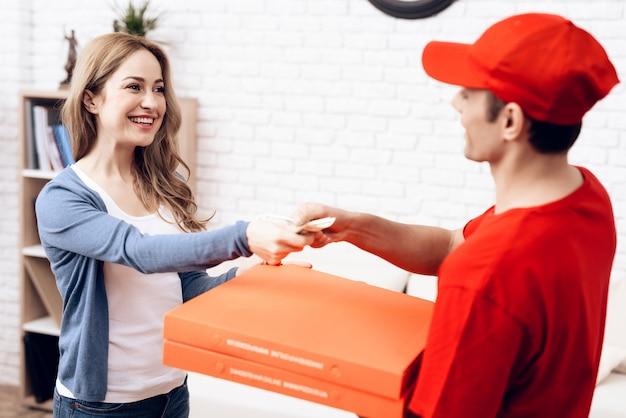 Smiling woman hands money pizza delivery man. Premium Photo