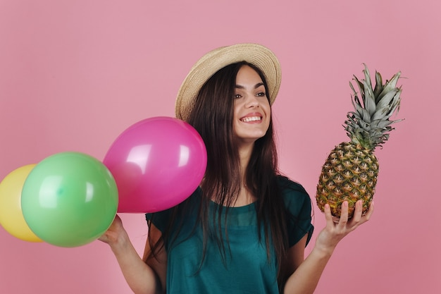 Smiling woman in a hat poses with colorful balloons and a pineapple Free Photo
