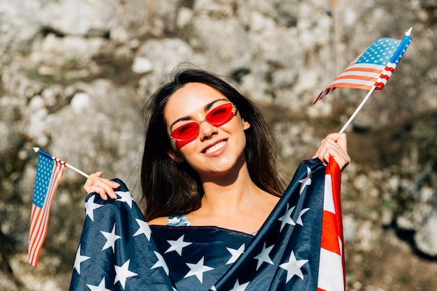 Smiling woman holding american flags in sunlight Free Photo