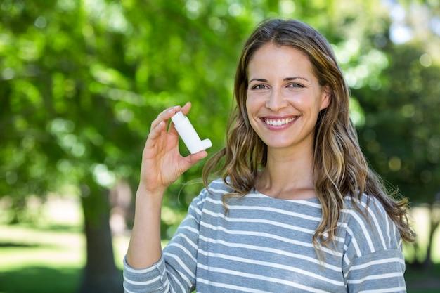 Улыбающиеся женщина, держащая астмы ингалятор Premium Фотографии