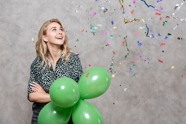 Smiling woman holding balloons surrounded by confetti Free Photo