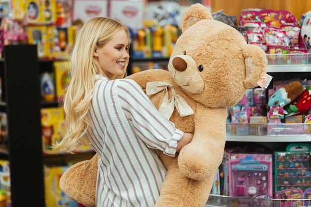 Smiling woman holding big teddy bear Free Photo
