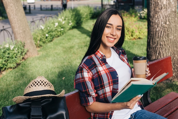 Smiling woman holding book and disposable coffee cup while sitting on bench at park Free Photo