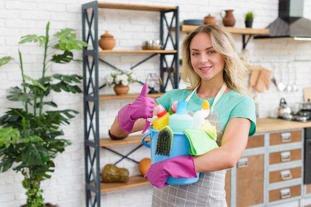 自宅に立っているthumbupジェスチャーを示すクリーニング製品のバケツを持って笑顔の女性 Premium写真