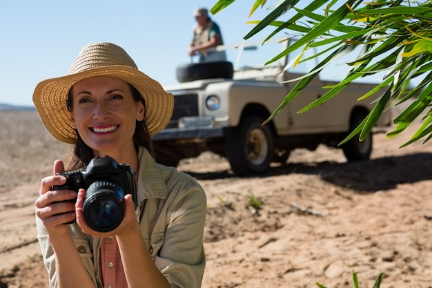 Smiling woman holding camera with man on off road vehicle Free Photo