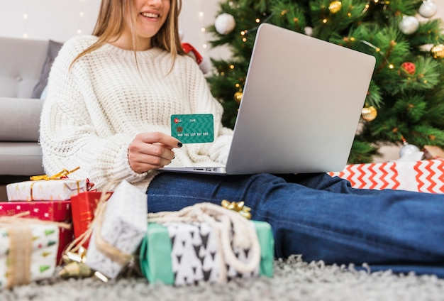 Smiling woman holding credit card and laptop Free Photo