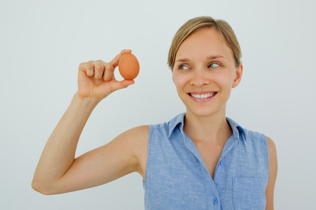 Smiling woman holding egg with two fingers Free Photo