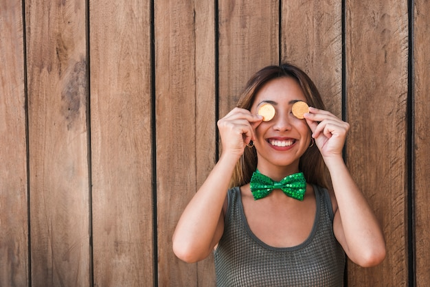 Smiling woman holding golden coins near eyes Free Photo