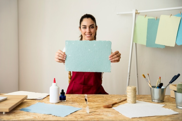 Smiling woman holding handmade blue paper Free Photo