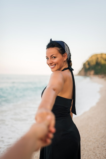 Smiling woman holding man's hand while walking on the beach. Premium Photo
