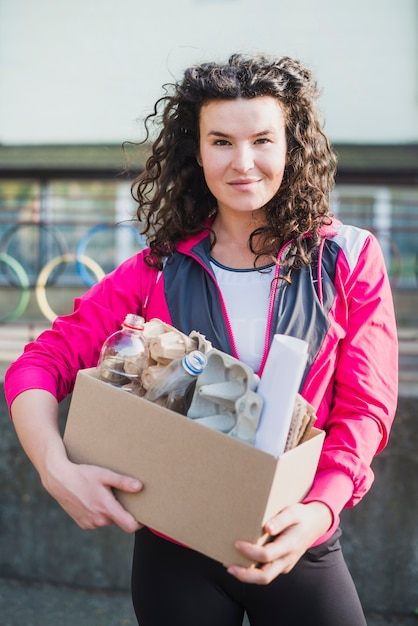 Smiling woman holding recycle cardboard box Free Photo