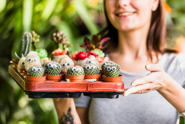 Smiling woman holding tray with green cactuses Free Photo