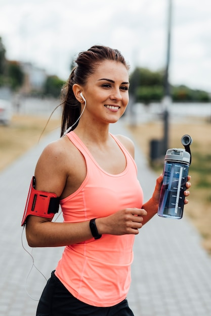Smiling woman holding a water bottle Free Photo