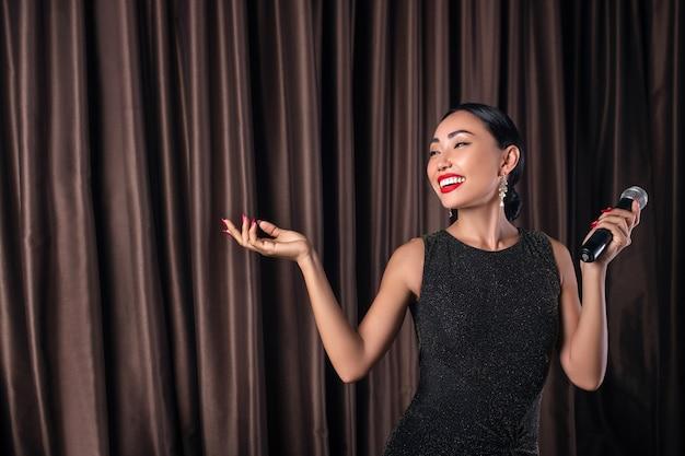 彼女の手にマイクと美しいドレスで笑顔の女性 Premium写真