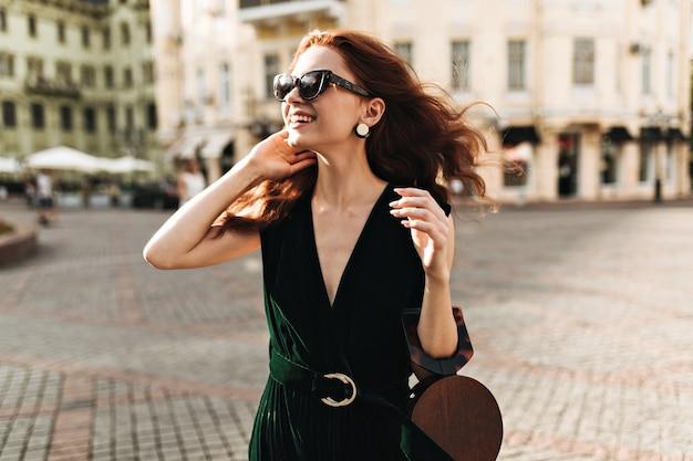 진한 녹색 옷을 입고 웃는 여자는 도시 산책을 즐긴다 무료 사진