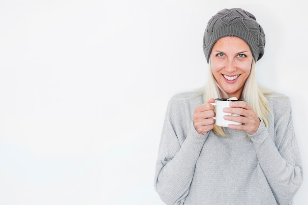Smiling woman in hat holding hot drink Free Photo