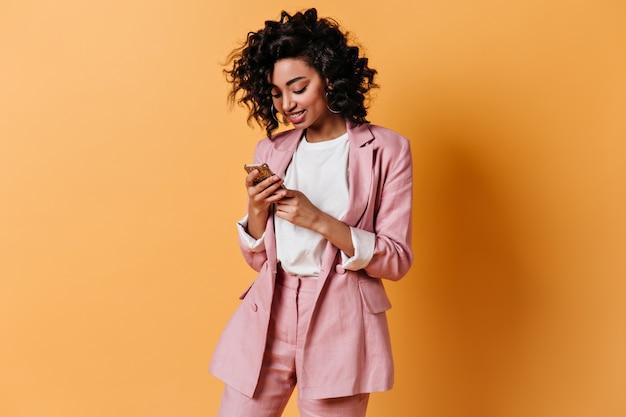 Улыбающаяся женщина в розовой куртке отправляет текстовое сообщение Бесплатные Фотографии