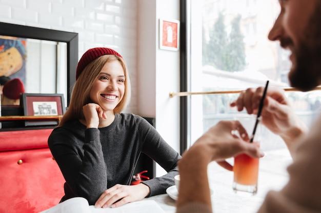 Улыбающаяся женщина в красной шляпе разговаривает с мужчиной Бесплатные Фотографии