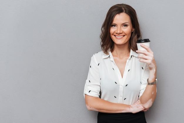 コーヒーを飲みながら灰色のカメラを見てシャツを着て笑顔の女性 無料写真