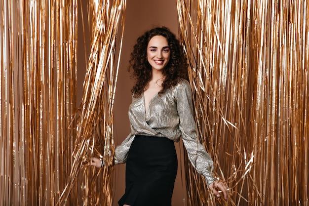 은색 옷을 입고 웃는 여자가 행복하게 금 배경에 포즈 무료 사진