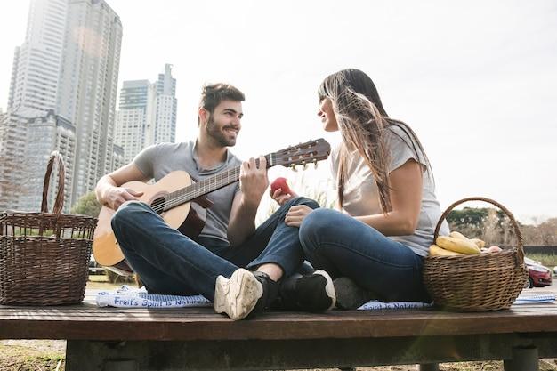 Улыбка женщины, глядя на человека, играющего на гитаре на пикнике Бесплатные Фотографии