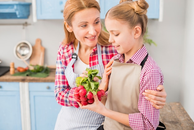 Smiling woman looking at her daughter holding fresh radish in hand Free Photo
