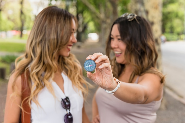 Smiling woman looking at her female friend showing compass near the camera Free Photo