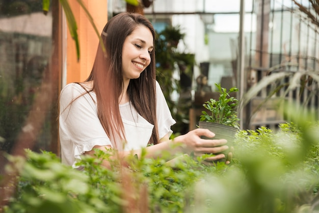 Smiling woman looking at potted plant in greenhouse Free Photo