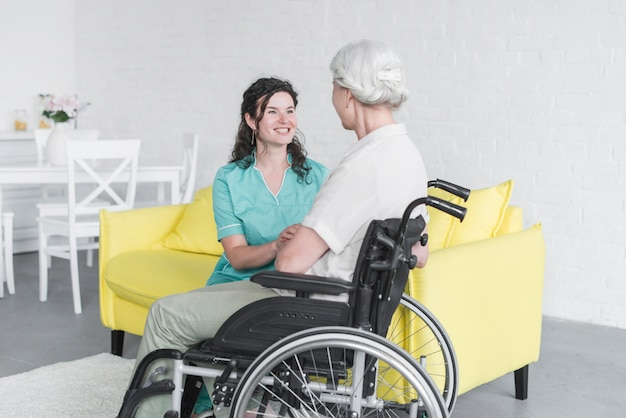 Smiling woman looking at senior woman sitting on wheel chair Free Photo