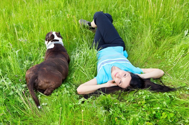 Smiling woman lying on the grass with dog Premium Photo