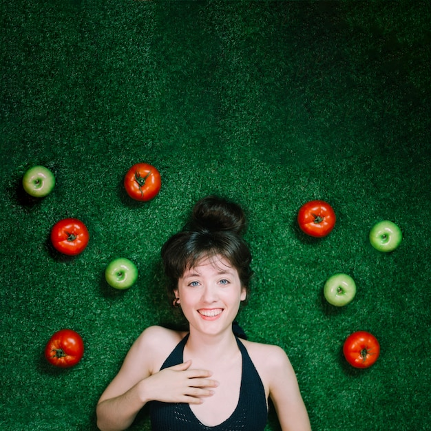Smiling woman near apples and tomatoes Free Photo
