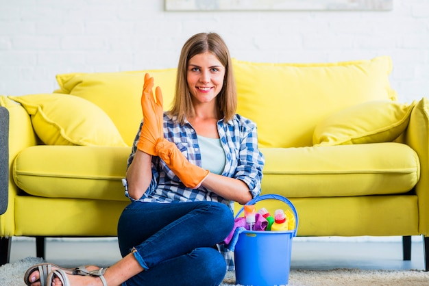 Smiling woman in an orange gloves sitting with cleaning equipments in the bucket Free Photo